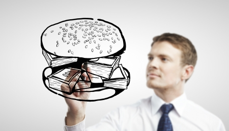 businessman drawing sandwich out of money photo
