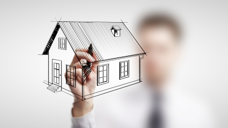 businessman drawing cottage on a white background photo