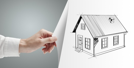 businessman hand turns gray page with house photo