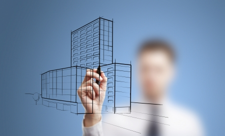 man drawing skyscrapers on a blue background photo