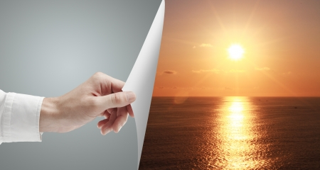 hand turn gray page to sunset over ocean photo