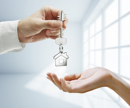 agents: passing key against backdrop of white room Stock Photo