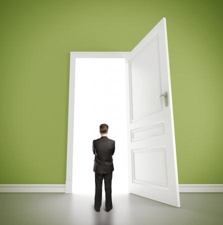 man in green room with doors open photo