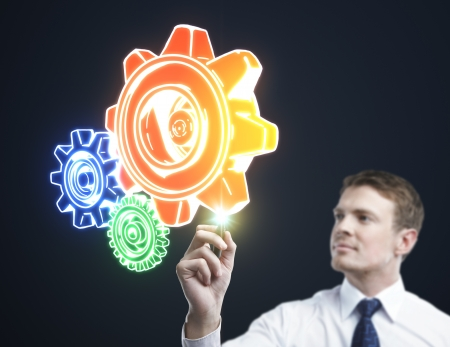 man drawing color gears on a blue background photo