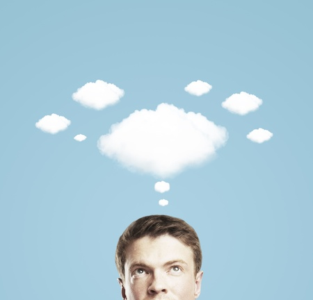 thought clouds: businessman and a cloud of thoughts on a blue background Stock Photo