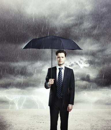 lloviendo: Hombre de negocios con paraguas bajo la lluvia Foto de archivo