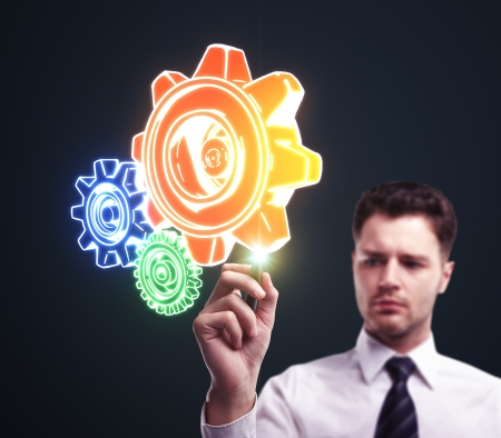 businessman drawing color  gears on a blue background Stock Photo - 15359190