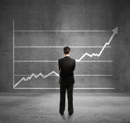 successful leadership: businessman looks at growth chart