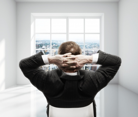 businessman sitting in chair in white room photo