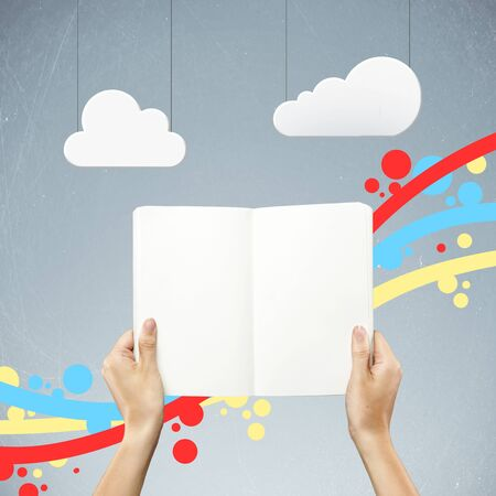 book in hand and abstract clouds Stock Photo - 15788326