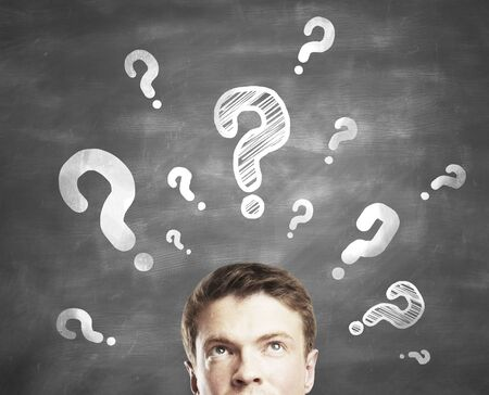 signo de interrogacion: hombre de negocios con signo de interrogación sobre un fondo gris Foto de archivo