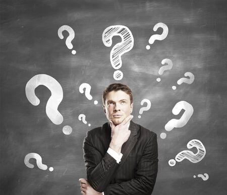 punto di domanda: l'uomo con il punto interrogativo su sfondo grigio Archivio Fotografico