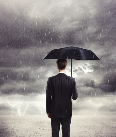 argent: Businessman with umbrella in rain Stock Photo