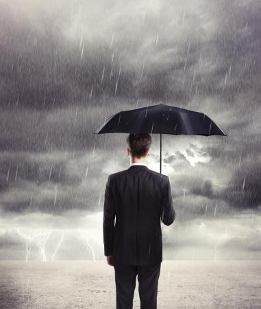 lluvia paraguas: Hombre de negocios con paraguas bajo la lluvia Foto de archivo