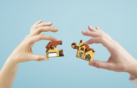 house in hand: two hands holding house puzzle Stock Photo