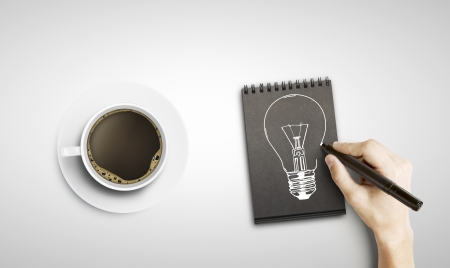drawing lamp in notepad and cup of coffee photo