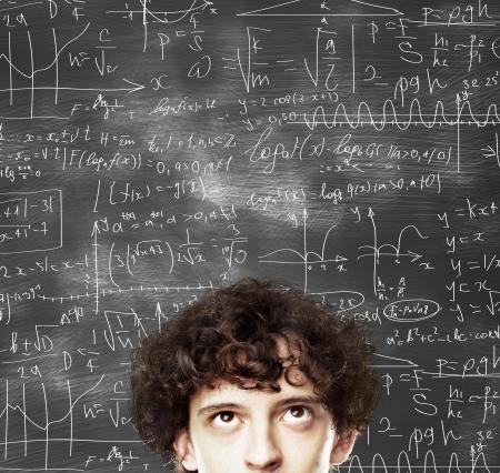signos matematicos: hombre de pensamiento contra el escritorio con fórmulas