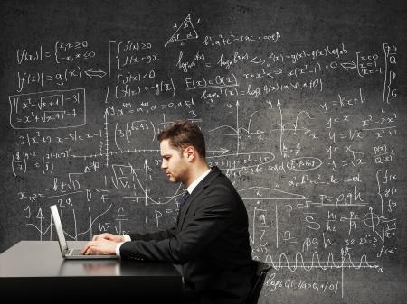 signos matematicos: hombre de negocios en un fondo de fórmulas Foto de archivo