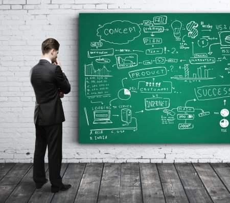 writing board: businessman looking at business strategy on board