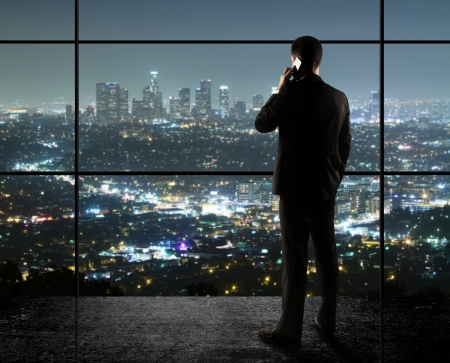 the window: businessman with phone looks in night city