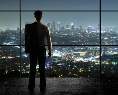 global city: businessman looks in night city