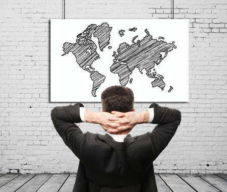 businessman sitting and map on wall photo