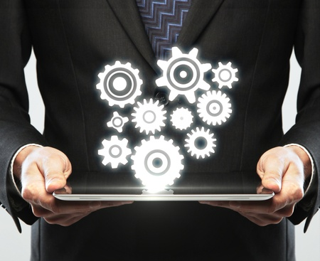 digital tablet in hand and gears symbol Stock Photo - 16032606