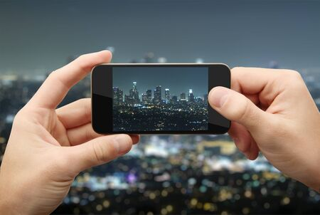 man photographs night city on a mobile phone photo