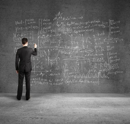 mathematics symbol: businessman  on  desk drawing formulas