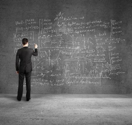 signos matematicos: hombre de negocios en f�rmulas de dibujo escritorio