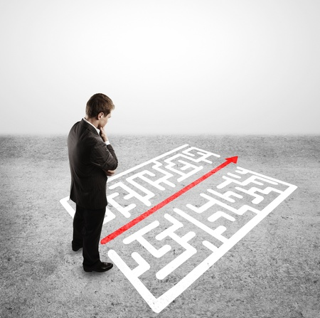 find solution: businessman in front of labyrinth with arrow Stock Photo