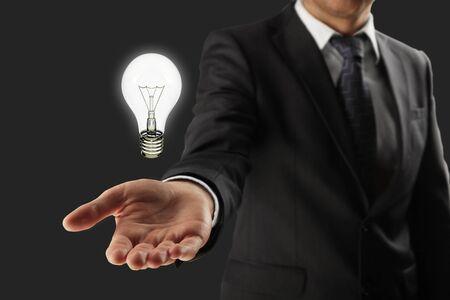 entrepreneur: man holding lightbulb in hand Stock Photo