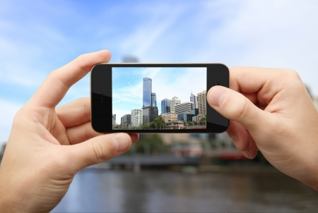 man photographs city on a mobile phone photo