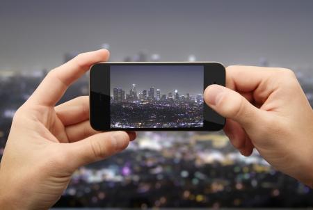 using mobile phone: businessman photographs night city on phone