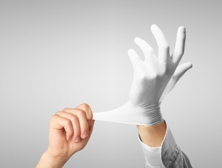 Doctor dress gloves on hands on gray background photo