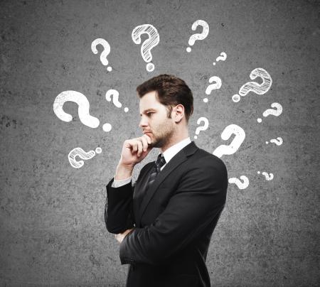 pensamiento creativo: hombre que tiene preguntas y muro de hormig�n