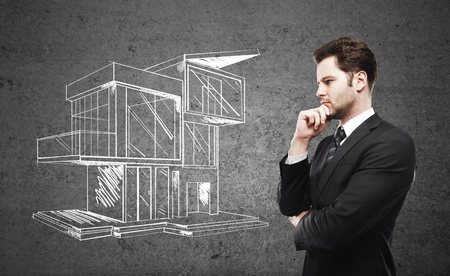 businessman thinking and drawing house photo