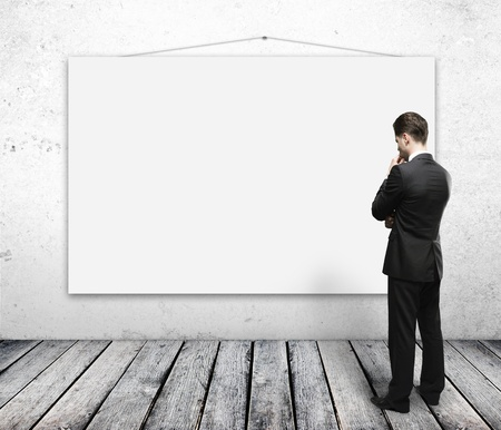 whiteboard: man looking empty poster on wall