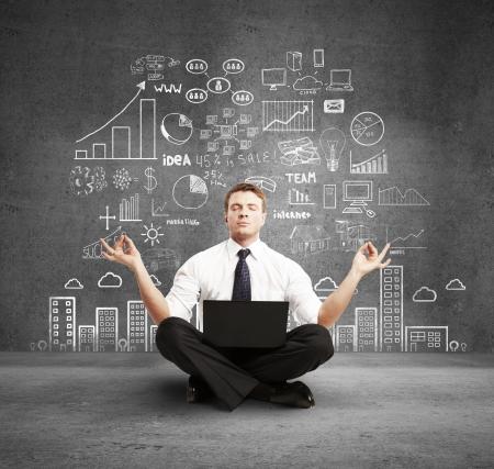 lluvia de ideas: hombre con la meditaci�n port�til y plan de negocios en la pared