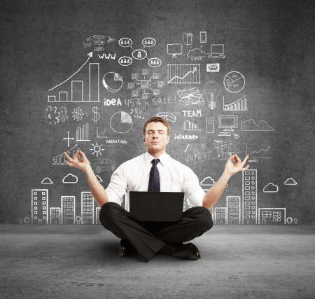 brainstorming: man with laptop meditation and business plan on wall Stock Photo