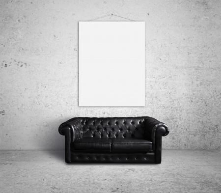 sofá en la habitación y un cartel vacío en la pared Foto de archivo