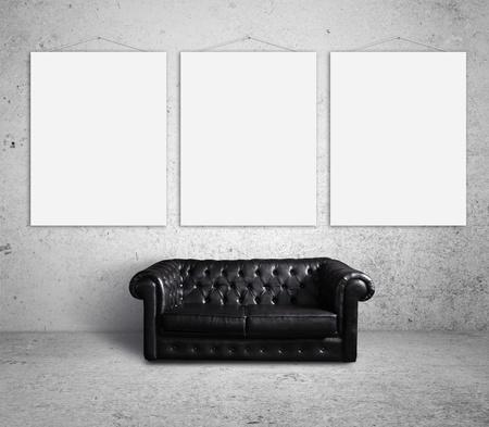 sofá en la habitación y tres carteles en la pared