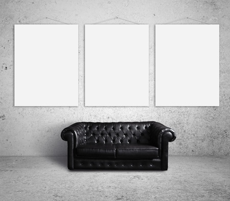 cracked concrete frame: sofa in room and three posters on wall Stock Photo