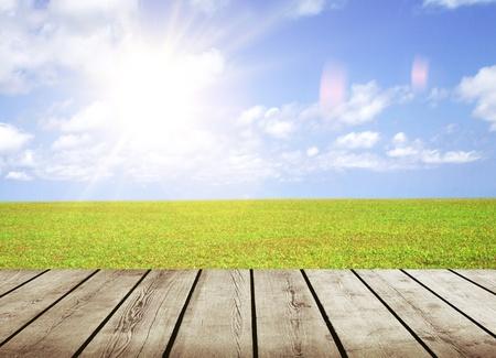 wood floor over green field under nice cloud sky background photo