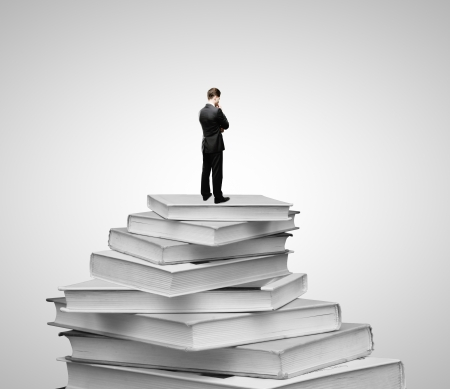 Businessman standing on a pile of books photo