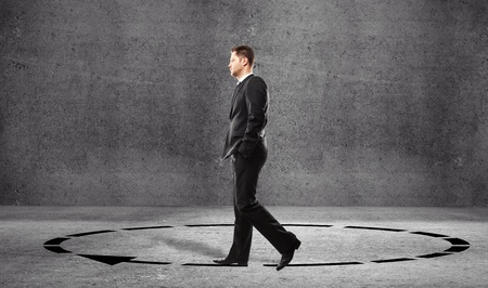 teaching material: Businessman walking in a circle in room Stock Photo