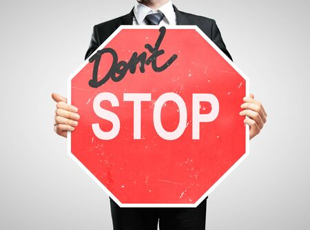 taxman: businessman holding a dont stop sign
