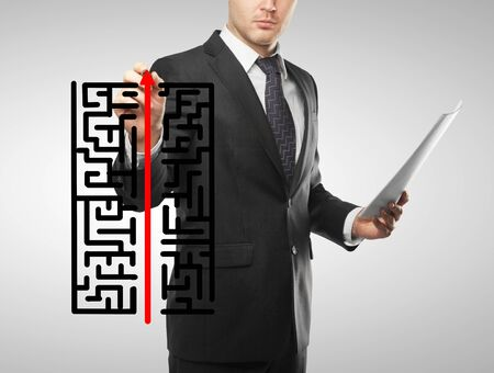 businessman drawing labyrinth and red arrow photo