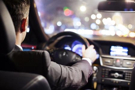 man driving a car at night photo