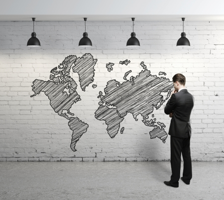 man looking at  world map on brick wall photo